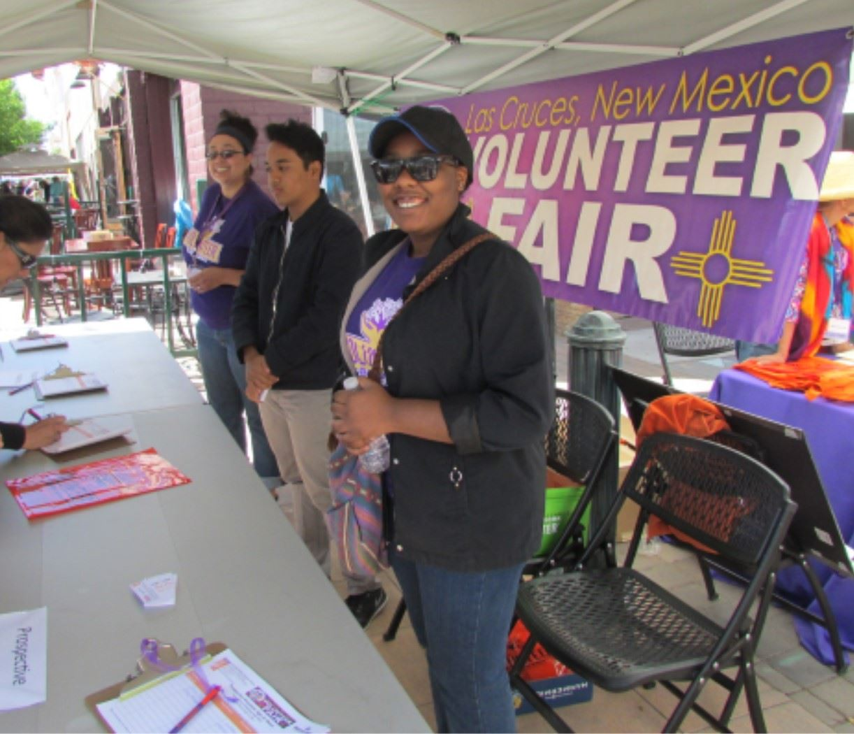 People pose a the Volunteer Fair booth